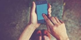 Händer som håller i en mobiltelefon